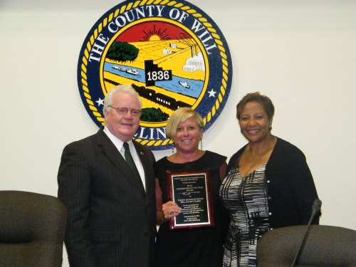 Will County Executive Larry Walsh congratulates Will County Clerk Nancy Schultz Voots (center) on being named Ambassador of the Year by the Will-Grundy Center for Independent Living during the July 15 County Board meeting. Will County Board member Denise Winfrey (right), who also serves as the president of the Board of Directors for the Will-Grundy Center for Independent Living, presented the award to Voots in recognition of her efforts to make handicapped accessible voting in all 445 County polling places.